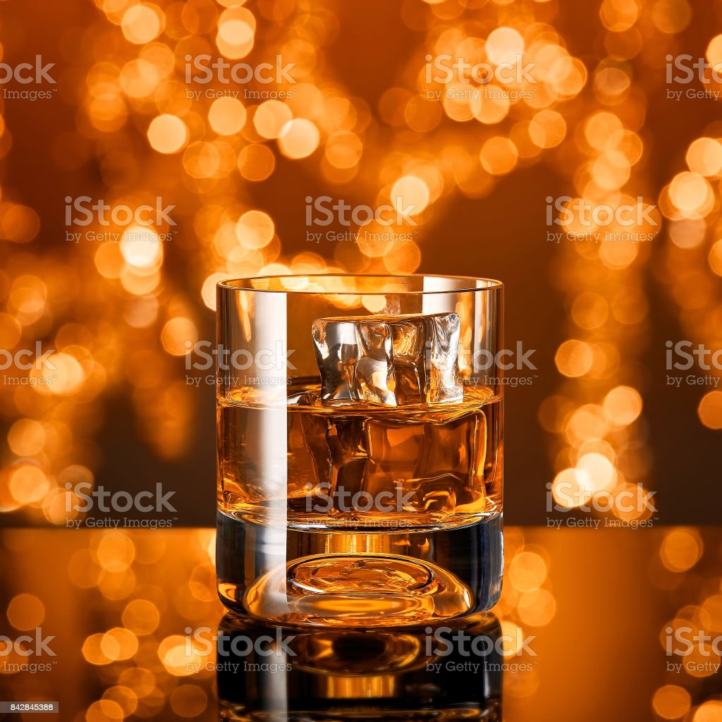 Glass of whiskey with ice cubes in front of christmas lights stock photo