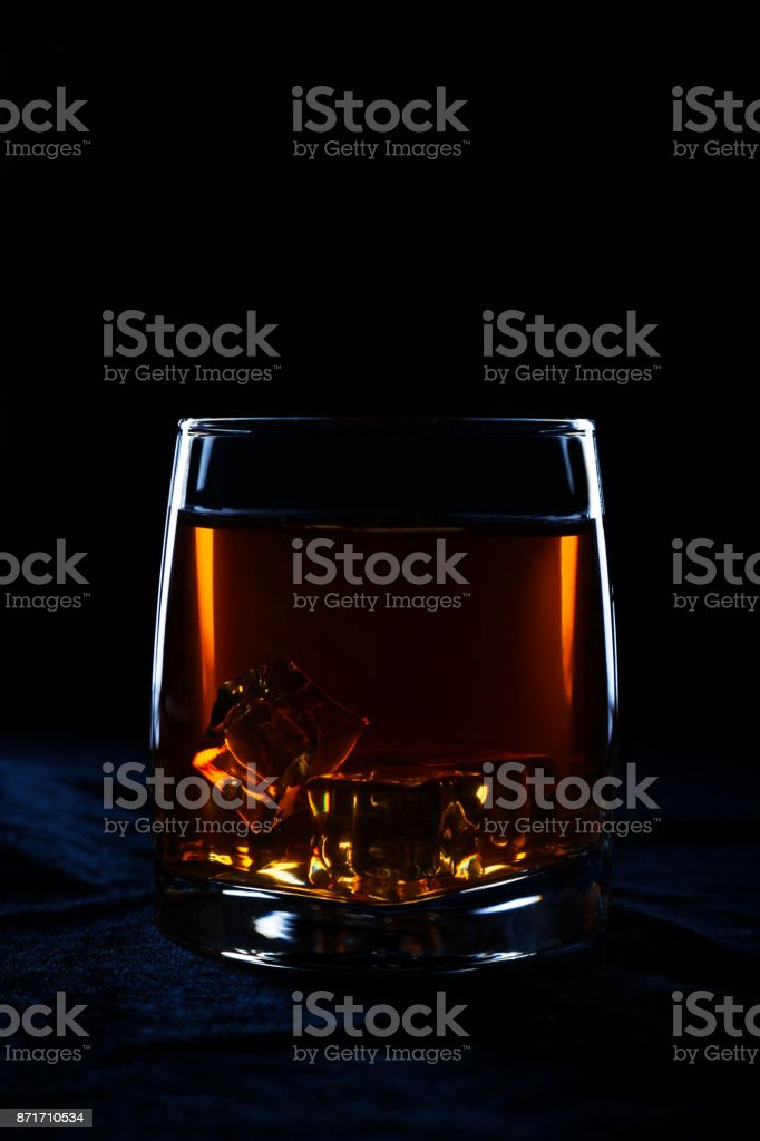 Glass of whiskey with ice cubes on black background stock photo