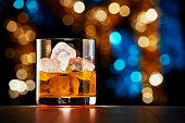istock Glass of whiskey with ice on colorful Christmas lights bokeh background 1179303998