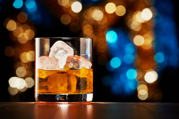 glass of whiskey with ice on colorful christmas lights bokeh background - alcool imagens e fotografias de stock