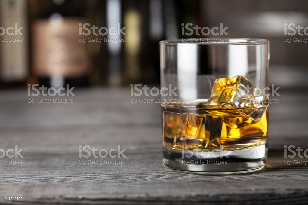 Glass of whiskey with ice on the bar rack stock photo