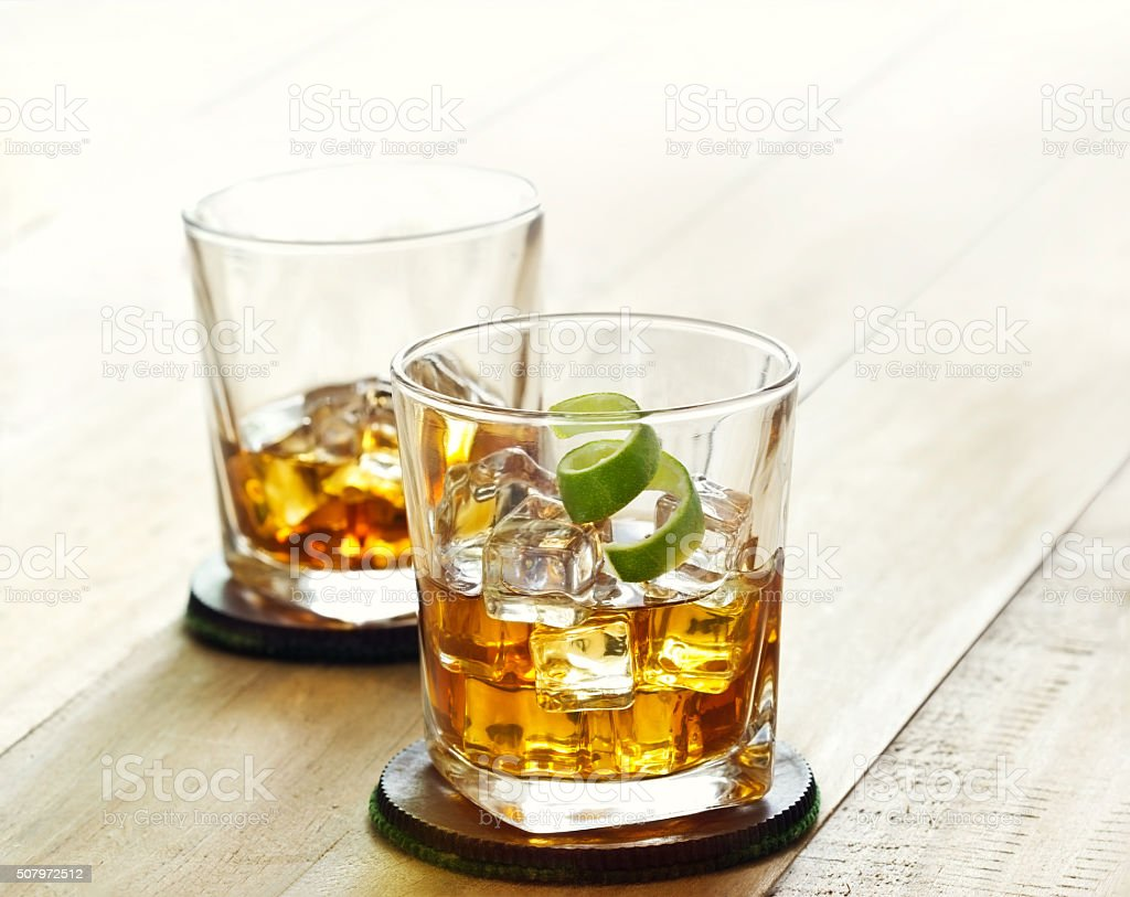 Glass of whiskey with ice on wooden background stock photo