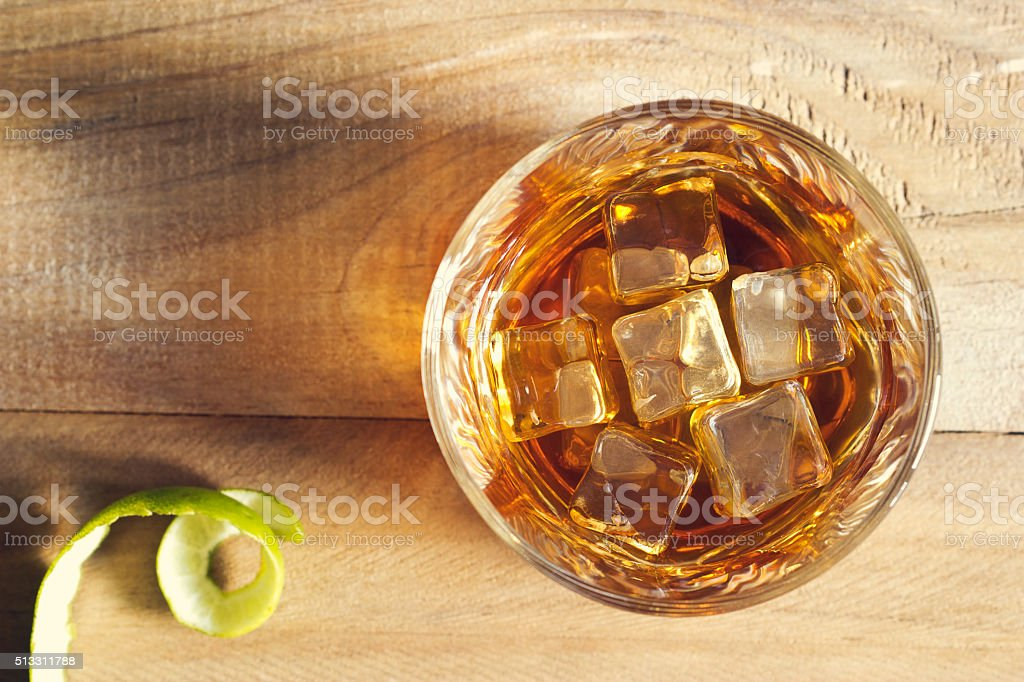Glass of whiskey with ice on wooden background, Top view stock photo