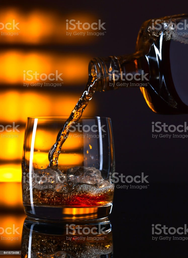 Glass of whiskey with ice stock photo