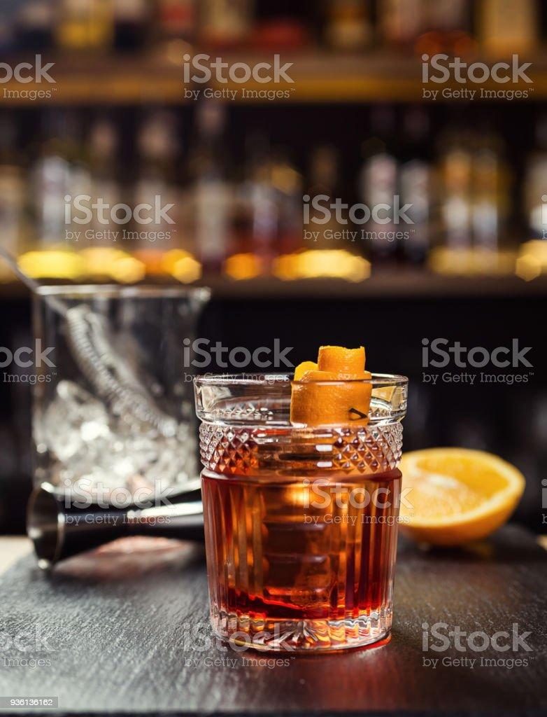 Glass of  whiskey (cognac or brandy) with lemon and ice cubes standing on the bar counter with a bottle on the background stock photo