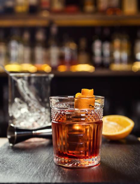 bardak viski (konyak ya da brendi) barda duran limon ve buz küpleri ile arka planda bir şişeyle sayaç - kokteyl i̇çki stok fotoğraflar ve resimler