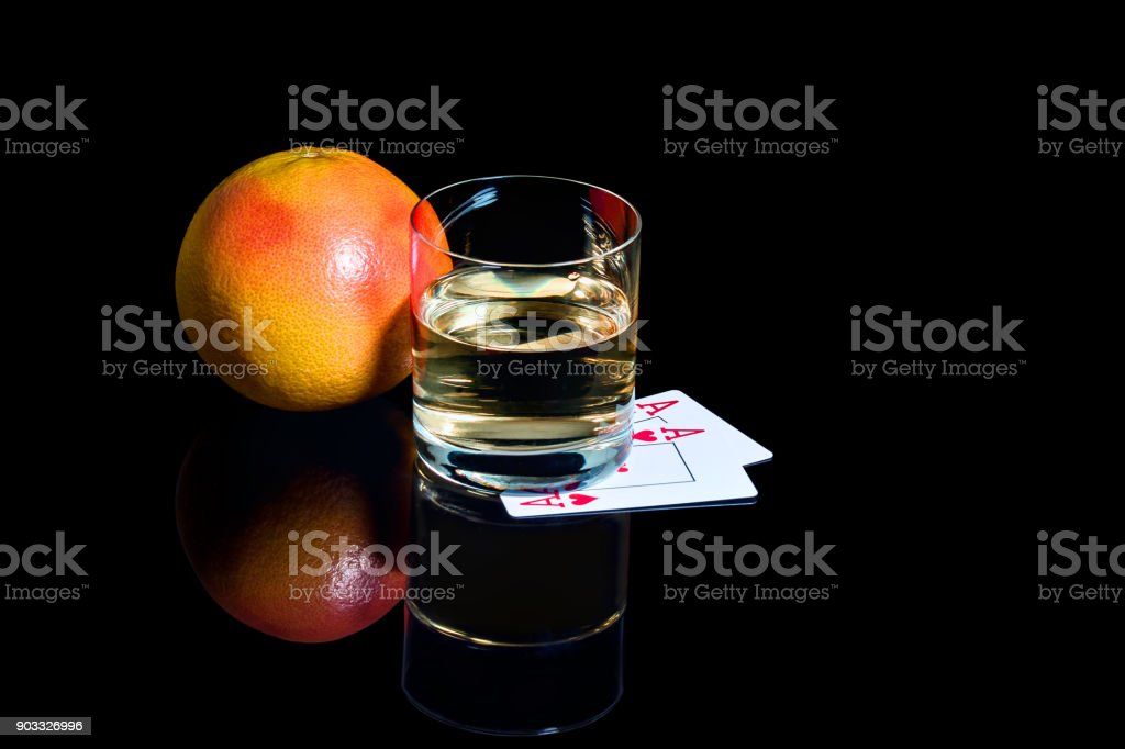 Glass of whiskey with playing cards and the grapefruit on the black background stock photo