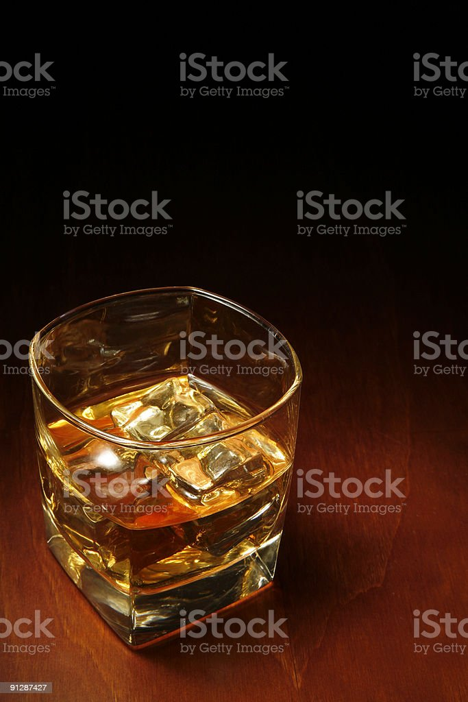 Glass of whisky and ice on a wood table royalty-free stock photo