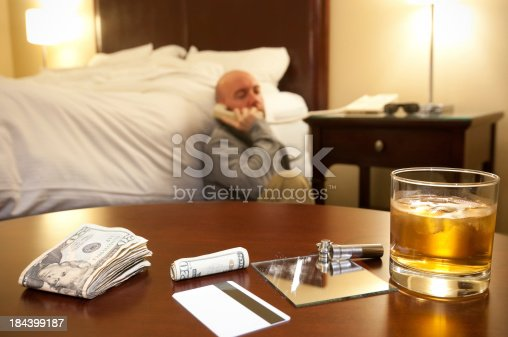 Man using the phone sitting on a hotel floor with a glass of whisky and simulated cocaine the foreground.