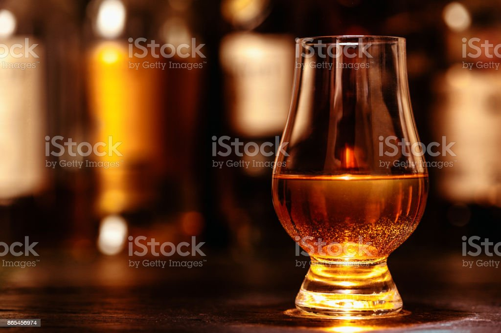Glass of whisky on table stock photo