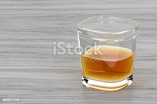 istock Glass of whisky on wood background 883031056