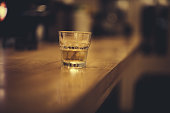Glass of Whiskey on Dark Wood Bar counter, no people.