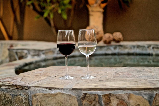 Glass of White and Red Wine Glass of Red and White Wine on ledge of hot tub cabernet sauvignon grape stock pictures, royalty-free photos & images