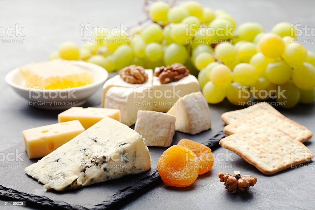 Glass of white wine and assorted cheese with grape stock photo