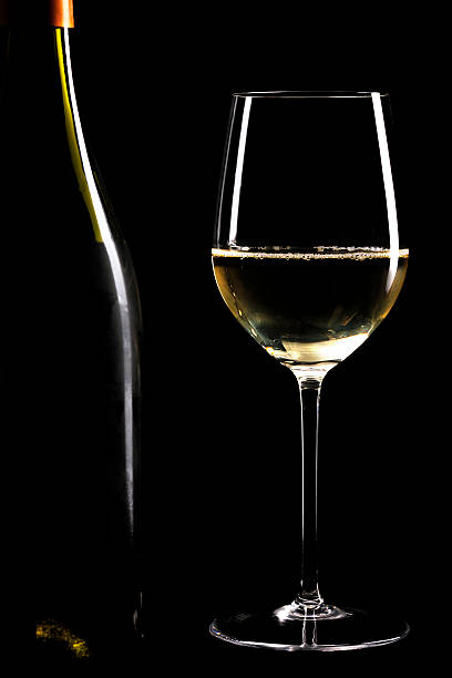 Glass of white wine and bottle stock photo