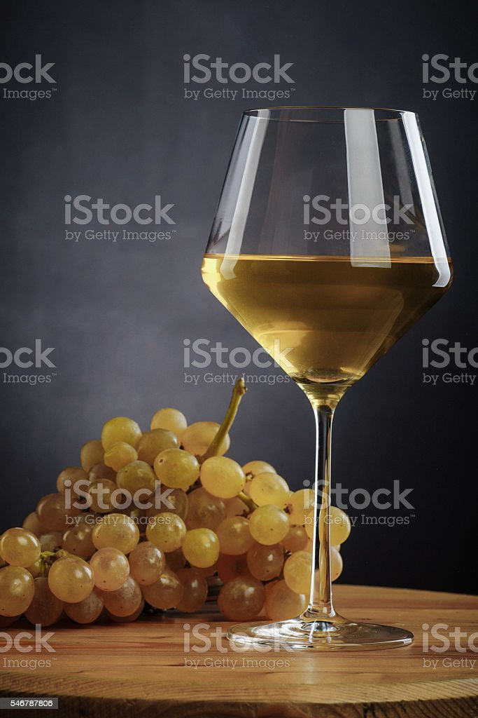 glass of white wine and grapes on a wooden table stock photo
