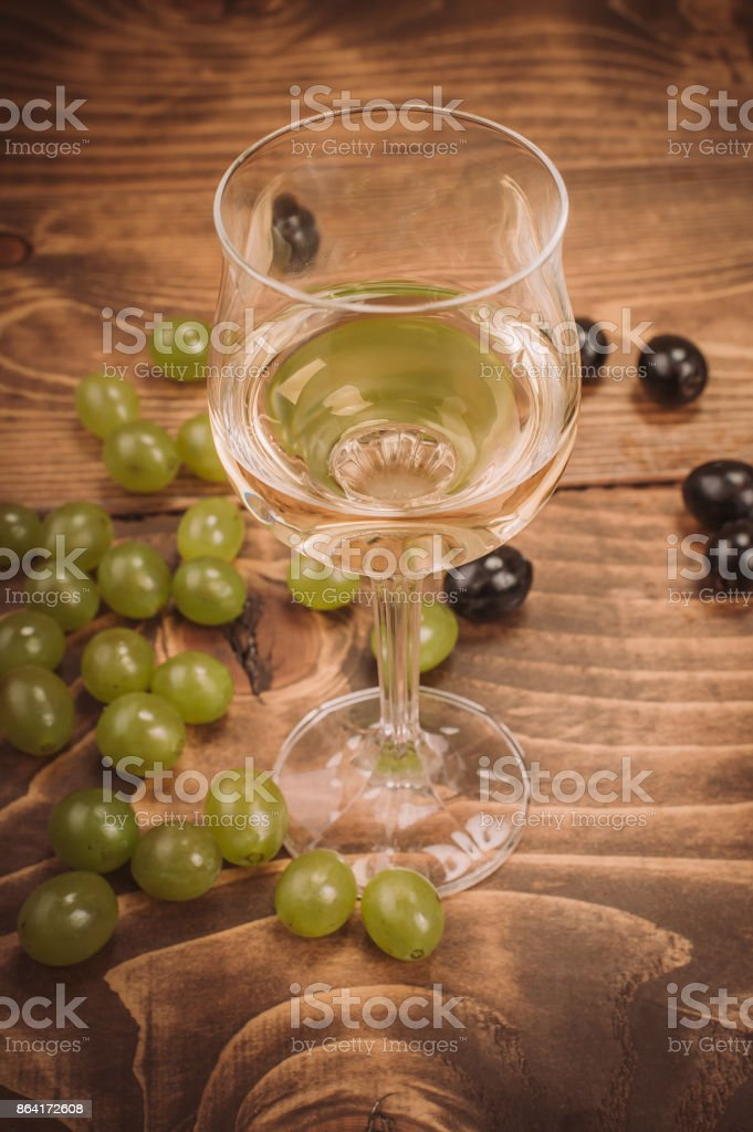 Glass of white wine and grapes on rustic wood table royalty-free stock photo