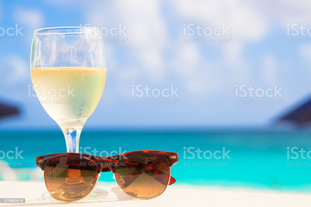 glass of white wine and sunglasses near the beach stock photo