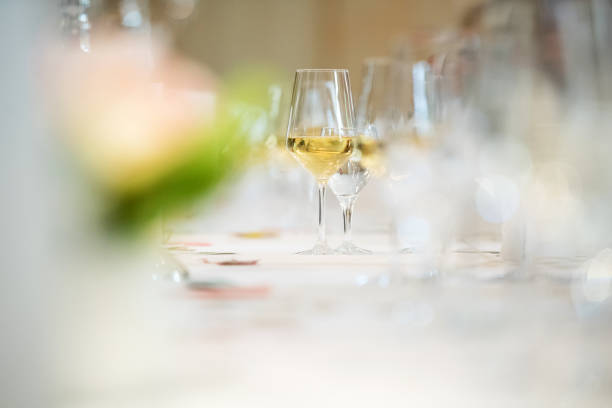 glass of white wine at table Germany: A glass of white wine at a long table. white wine stock pictures, royalty-free photos & images