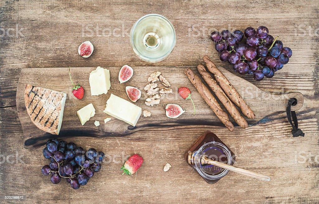 Glass of white wine, cheese board, grapes, figs, strawberries, honey stock photo
