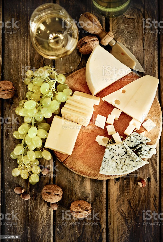 Glass of white wine, cheese, nuts and grapes stock photo