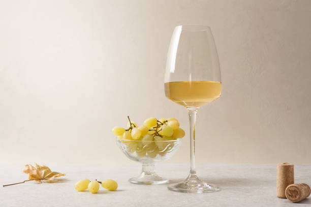 A glass of white wine, grapes and corks on the table. Light background. stock photo