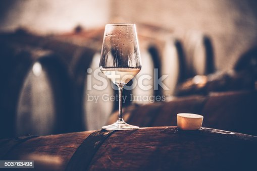 Glass of white wine on a barrel