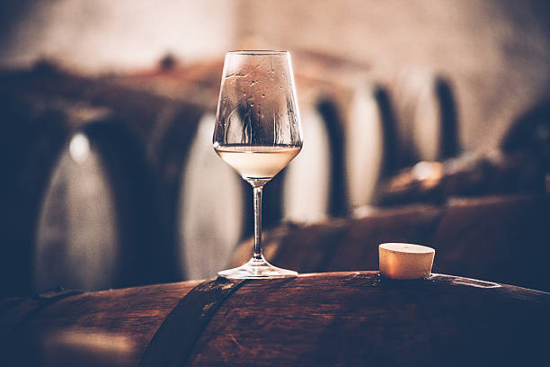 Glass of White Wine on a Barrel in Wine Cellar Glass of white wine on a barrel cellar stock pictures, royalty-free photos & images