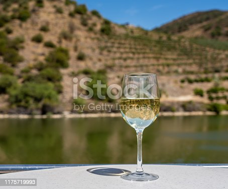 Glass of white wine for tasting on deck of cruise boat on the river in the Douro valley in Portugal