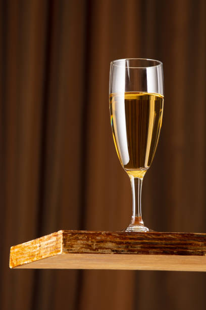 A glass of white wine on a vintage wooden bar counter with copy space. Shallow depth of field. Background blurred stock photo