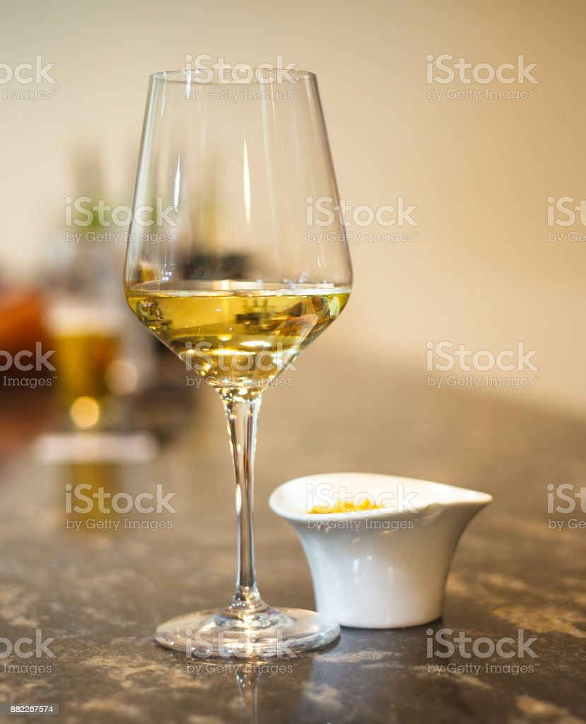 Glass of white wine on bar stock photo