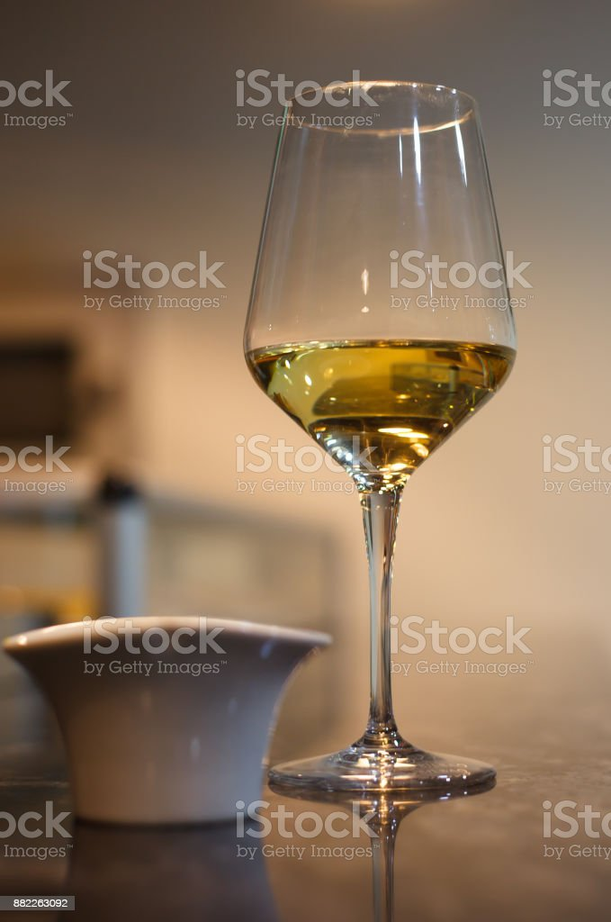 Glass of white wine on bar with small bowl stock photo