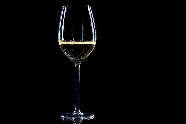 vaso de vino blanco sobre fondo negro - foto de stock