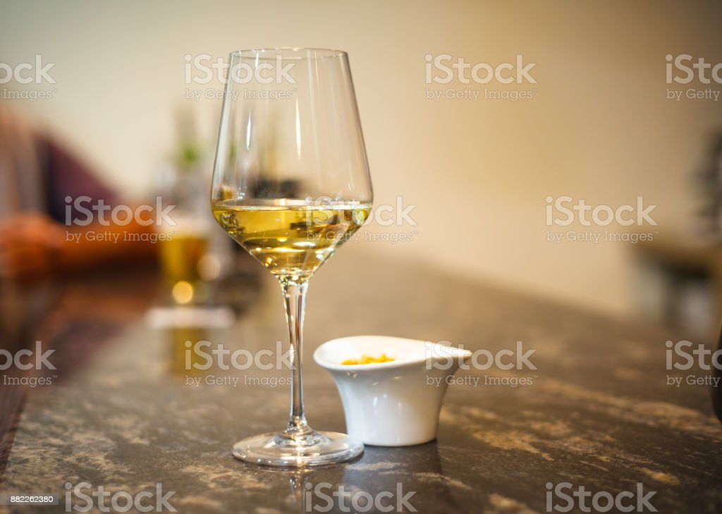 Glass of white wine on long bar stock photo