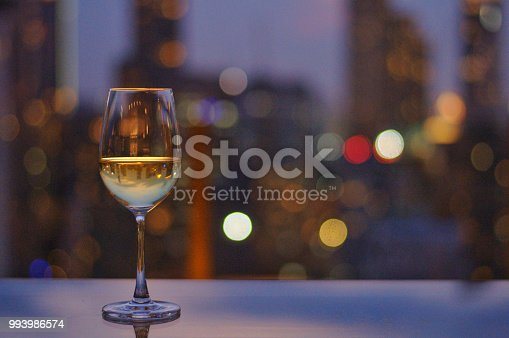 A glass of white wine on table of rooftop bar with colorful bokeh of city light and space for text.