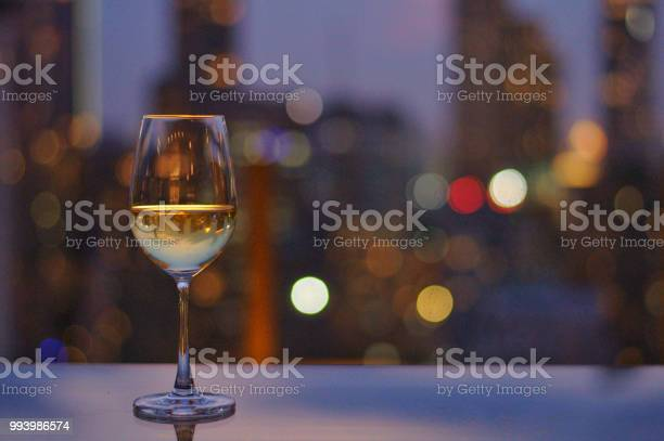 Glass of white wine on table of rooftop bar with colorful bokeh picture id993986574?b=1&k=6&m=993986574&s=612x612&h= qjbar1laesoct3ut1ypybjvx4mb 5ggidqws0kkd6o=