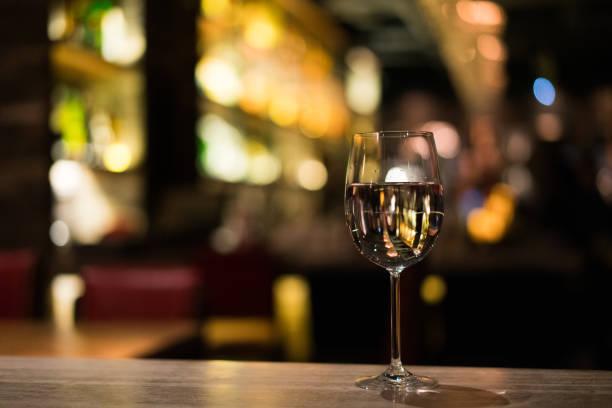 een glas witte wijn op de balk teller - happy hour stockfoto's en -beelden