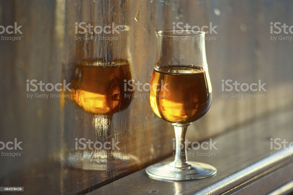 Glass of white wine reflects in wooden cask stock photo