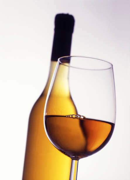 Glass of White Wine with Bottle in Background  calvados stock pictures, royalty-free photos & images