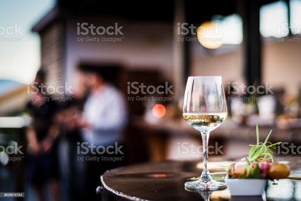 glass of white wine with gourmet food tapa snacks in outdoors bar at sunset - foto stock