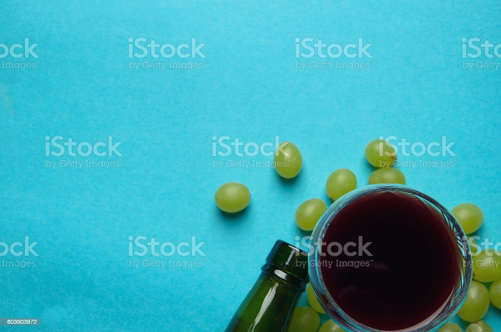 glass of wine and grapes, isolated on blue stock photo