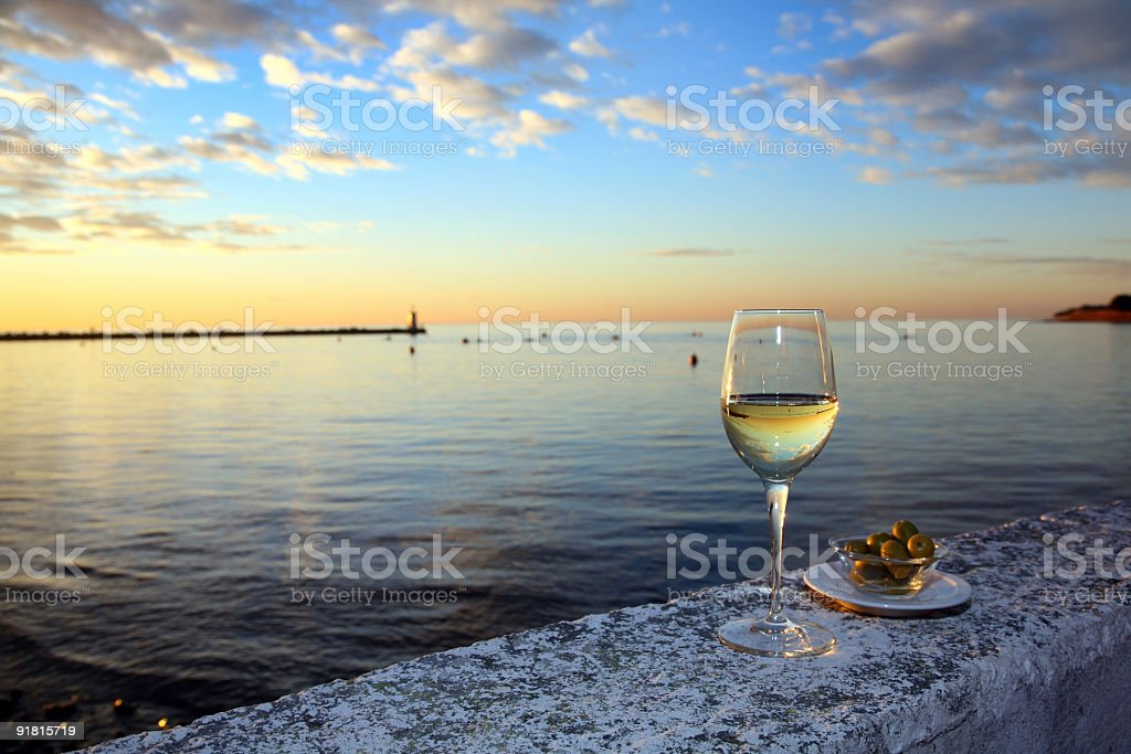 Glass of wine and olives by the sea stock photo