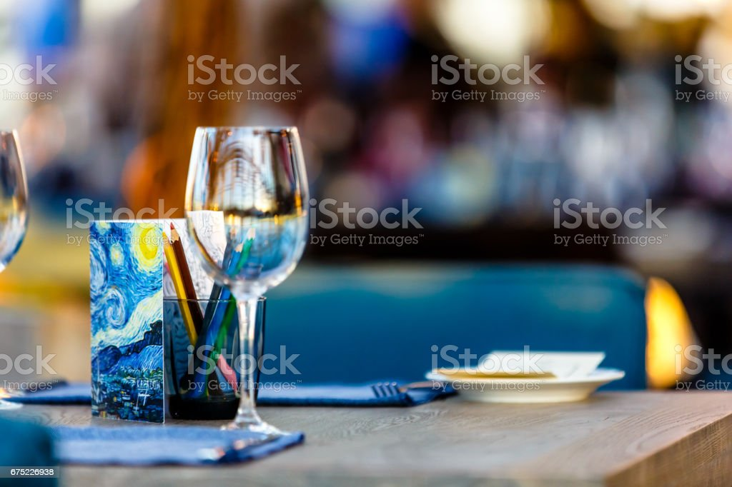 A glass of wine and some pencils is on the table in the restaurant. Illustration for the theme 'children in the restaurant.' royalty-free stock photo