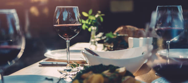 Glass of wine at dining table stock photo