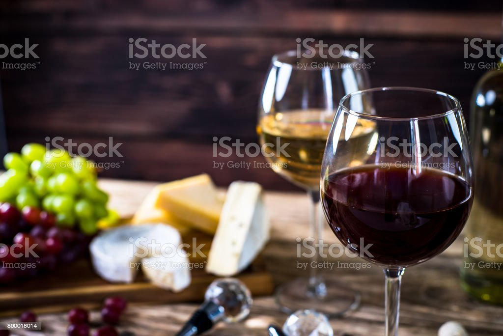Glass of  wine, cheeses and grapes on brown wooden background stock photo