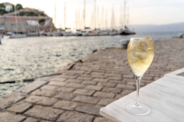 Glass of wine in Kamini on Hydra Island, Greece A glass of white wine with ice, at sunset, in the harbor of the enchanting Greek Island of Hydra. rymdraket stock pictures, royalty-free photos & images