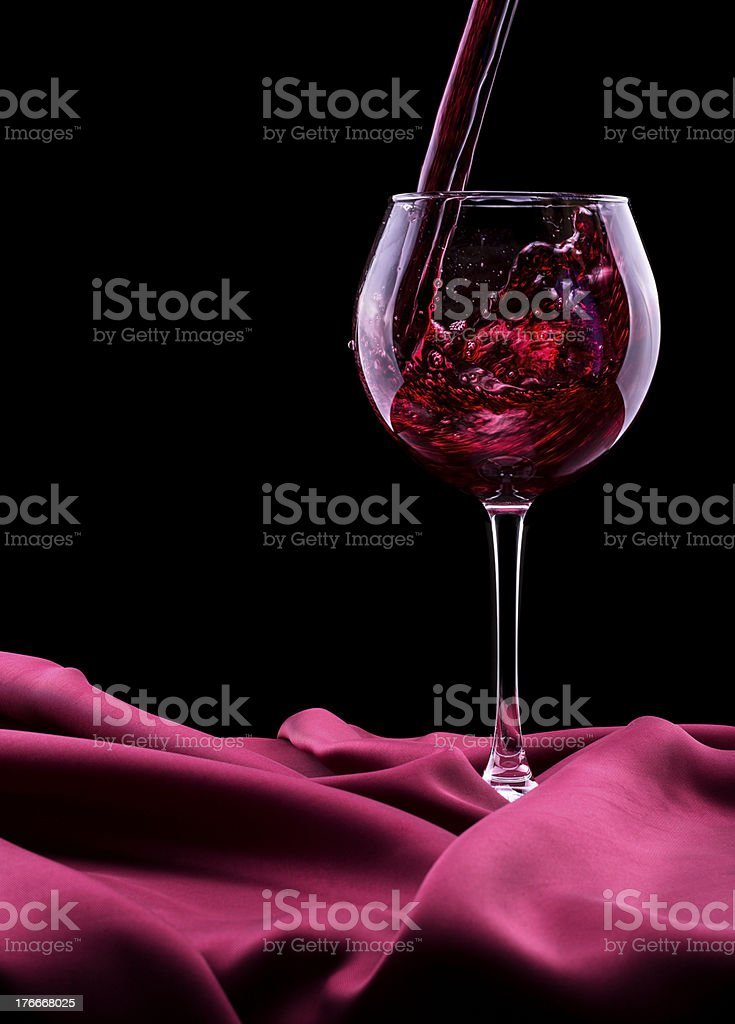 Glass of wine on red silk royalty-free stock photo