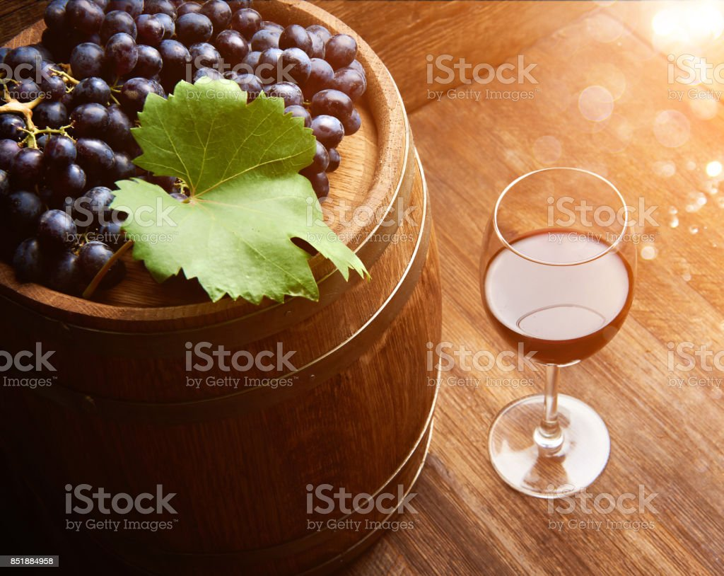Glass of wine on wooden table with ripe grapes of wine and wooden barrel. stock photo