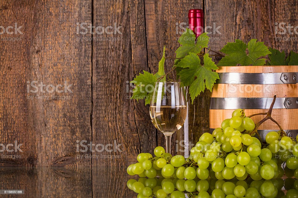 Glass of wine with barrel white bottle hidden by grapeleaves stock photo