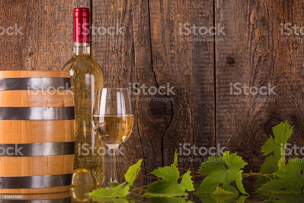 Glass of wine with white bottle and barrel stock photo